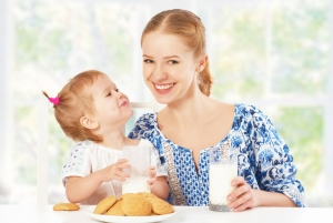 37554704 - happy family mother and baby daughter  child girl at breakfast: biscuits with milk